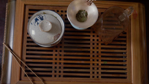 Close up hands of tea lover taking green tea cup from wooden table top view Live Action