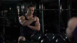 Bodybuilder looking at himself in mirror after workout, satisfied with results Live Action