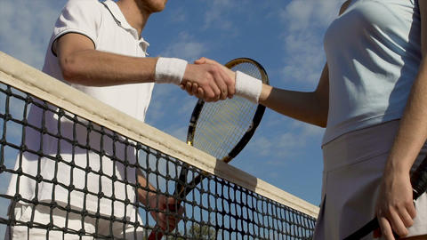 Tennis players handshaking after match on blue sky background, competition Live Action