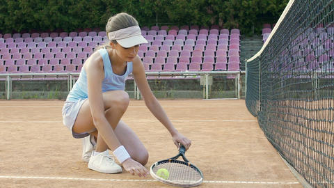 Cute female tennis player tying her sport shoes laces before starting match Live Action