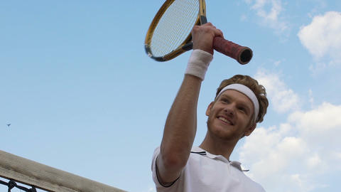 Proud male tennis player near net demonstrating... Stock Video Footage