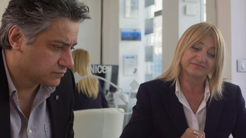 Man and woman choosing holiday trip at travel agency, manager flipping catalog Live Action