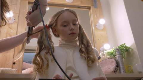 Beautiful girl while curling long hair with hair iron in hairdressing salon low Footage