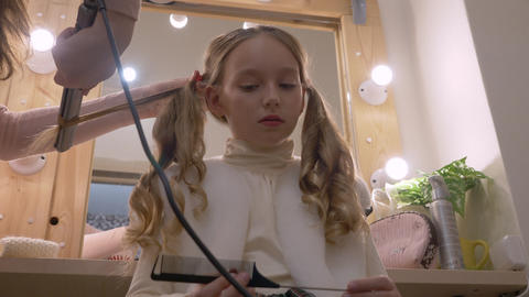 Beautiful girl while curling long hair with hair iron in… Stock Video Footage
