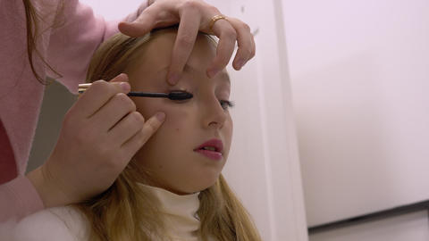 Portrait girl teenager while applying mascara on eyelashes in makeup studio Footage