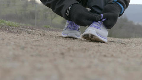 Athlete runner in winter sportswear tying laces for jogging 영상물