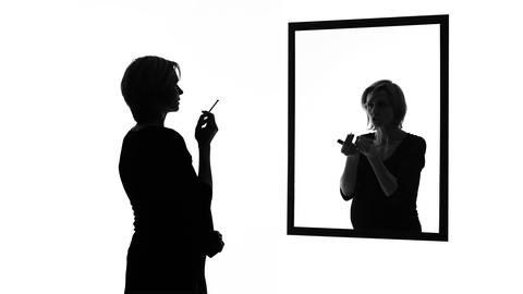 Conscience-stricken pregnant woman smoking cigarette in front of mirror, habits Live Action