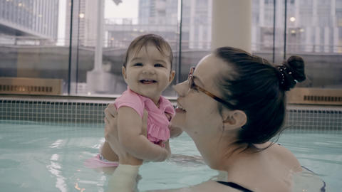 4K Mother and baby girl playing in a pool Footage