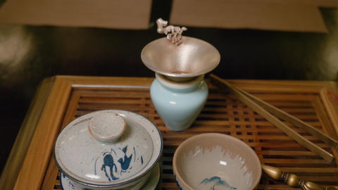 Tablewar bowl, cup and sieve for chinese tea on wooden table close up Live Action
