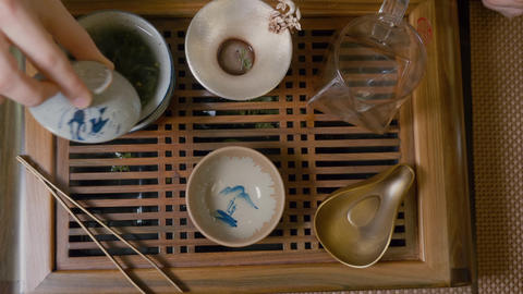 Master pours hot water in bowl with green tea top down view. Tea ceremony Live Action