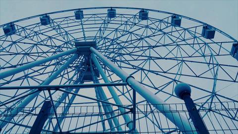 Moving Ferris wheel behind a grid Archivo