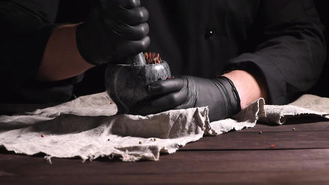 Chef in black latex gloves holds a stone mortar with a mixture of peppers Archivo