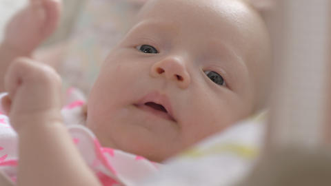 Indoor portrait of lovely active two months baby girl Live Action