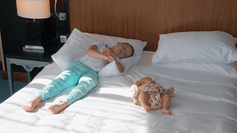 Baby girl with elder brother on the bed at home Live Action