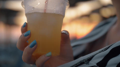 Woman drinking iced lemonade outdoor at sunset Footage