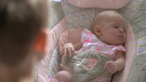 Elder brother lulling baby sister to sleep in rocking chair Footage