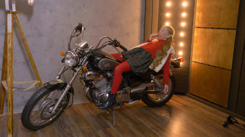 Young girl lying on motorcycle while posing on photo session in photo studio Footage