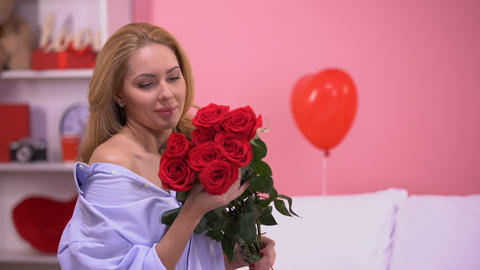 Happy beautiful woman holding bunch of red roses and smiling to camera, romance Footage