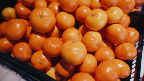 Detailed shot of a freshly picked orange tangerines in the grocery department of Footage