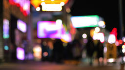 Crowd of people waling on the sidewalk of a city at night with blurry lights and 영상물
