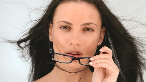 Portrait of a girl with long hair, she poses in glasses on a white background ,  Footage