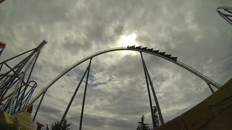Roller Coaster Ride against cloudy sun Footage