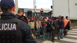 POLICEMAN LOOKING AT GROUP OF MIGRANTS NEAR TRAIN STATION Footage