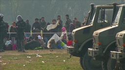 MILITARY TRUCKS WITH MIGRANTS AND POLICE IN BACKGROUND EU REFUGEES Footage