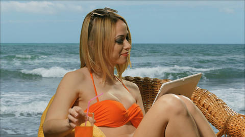 Girl blonde on the beach in swimsuit drinking juice and uses a tablet Footage