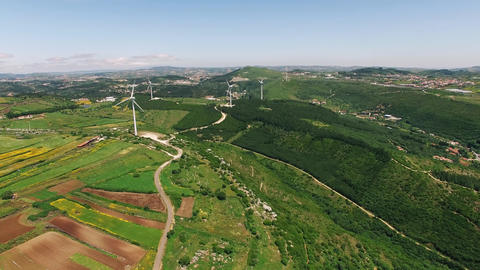 Wind power plants on a green hills aerial drone ビデオ