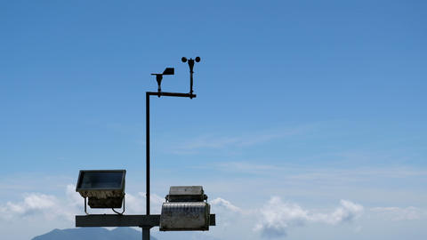 Anemometers with spotlight on blue sky, cloud and mountain background, UHD 4K Footage
