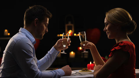 Sweet passionate couple on romantic date drinking champagne and clinking glasses Footage