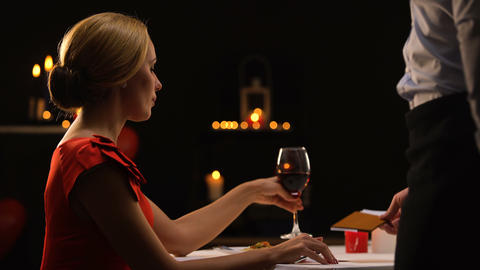 Waiter giving pretty lady bill, luxurious restaurant, consumer rights protection Live Action