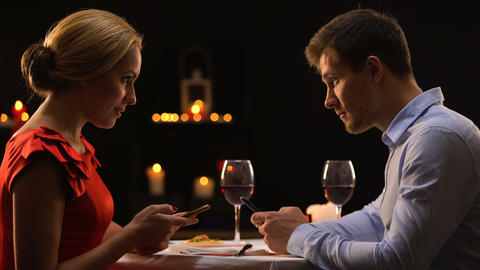 Couple in restaurant ignoring each other scrolling smartphones, gadget addiction Live Action