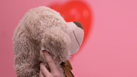 Happy woman hugging teddy bear, thinking with tenderness about beloved boyfriend Live Action