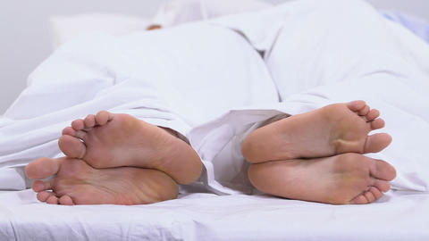 Feet of couple lying in bed under duvet, calluses and corns, fungal disease Footage