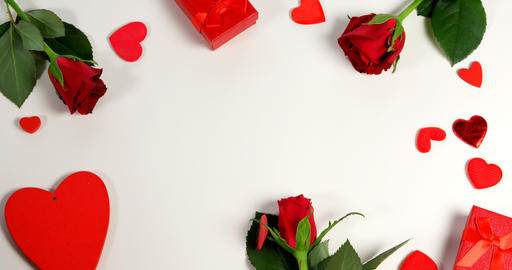 Red roses, gift boxes and heart shape of confetti on white surface in circle formation 4k Live Action