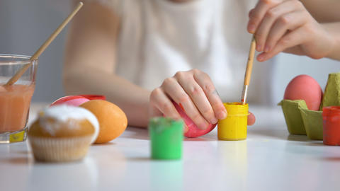Girl painting Easter egg with yellow color, family traditions, art school lesson Footage
