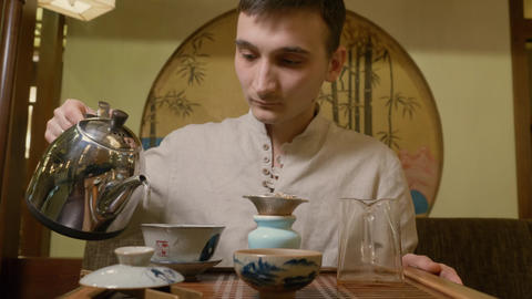 Tea master pouring hot water from kettle to gaiwan for brewing tea at ceremony Live Action