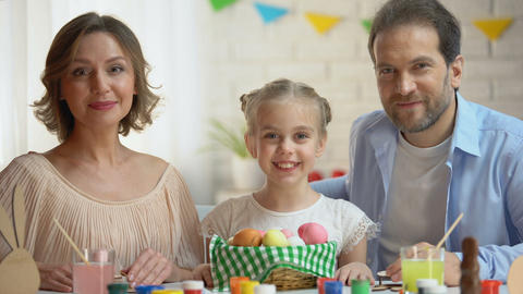 Friendly family posing at camera with basket of brightly colored Easter eggs Footage