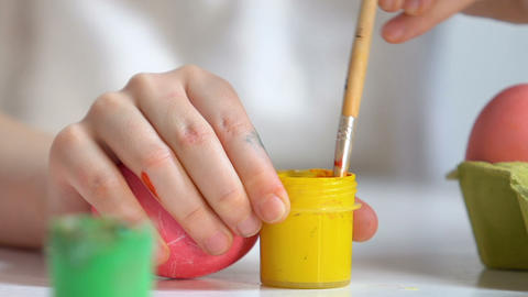 Children hands preparing yellow paint to draw pattern on egg, Easter preparation Live Action
