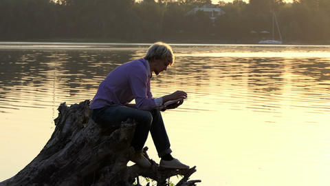 Future scientist sits on a lake bank and reads a manual Footage