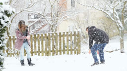 Young couple making, playing, throwing snowballs in snow, snowing weather Archivo