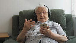 Old woman is listening music on a smartphone Live Action