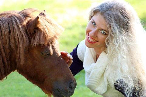 funny blonde girl strokes pony muzzle. Close-up Photo