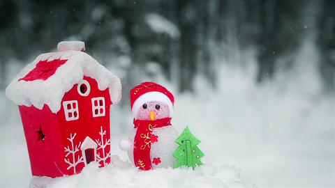 Christmas composition snowman near the red house in the forest HD Archivo