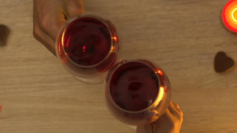 Couple clinking wine glasses during romantic evening, be my valentine, top view Live Action