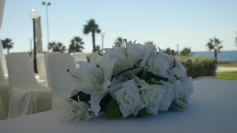 Closeup wedding bouquet of white lilies and white roses decorate tablecloth on Archivo