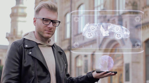 Smart young man with glasses shows a conceptual hologram chassis Footage