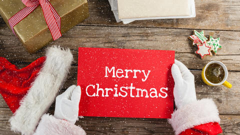 Video composition with snow over santa holding red card with greetings Animation